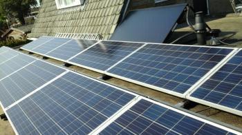 Blauwe zonnepanelen en zonneboiler geplaatst op plat dak te Odoorn (Drenthe) in september 2016