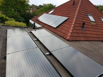 Zwarte zonnepanelen geplaatst op schuin en plat dak te Assen (Drenthe) in september 2016