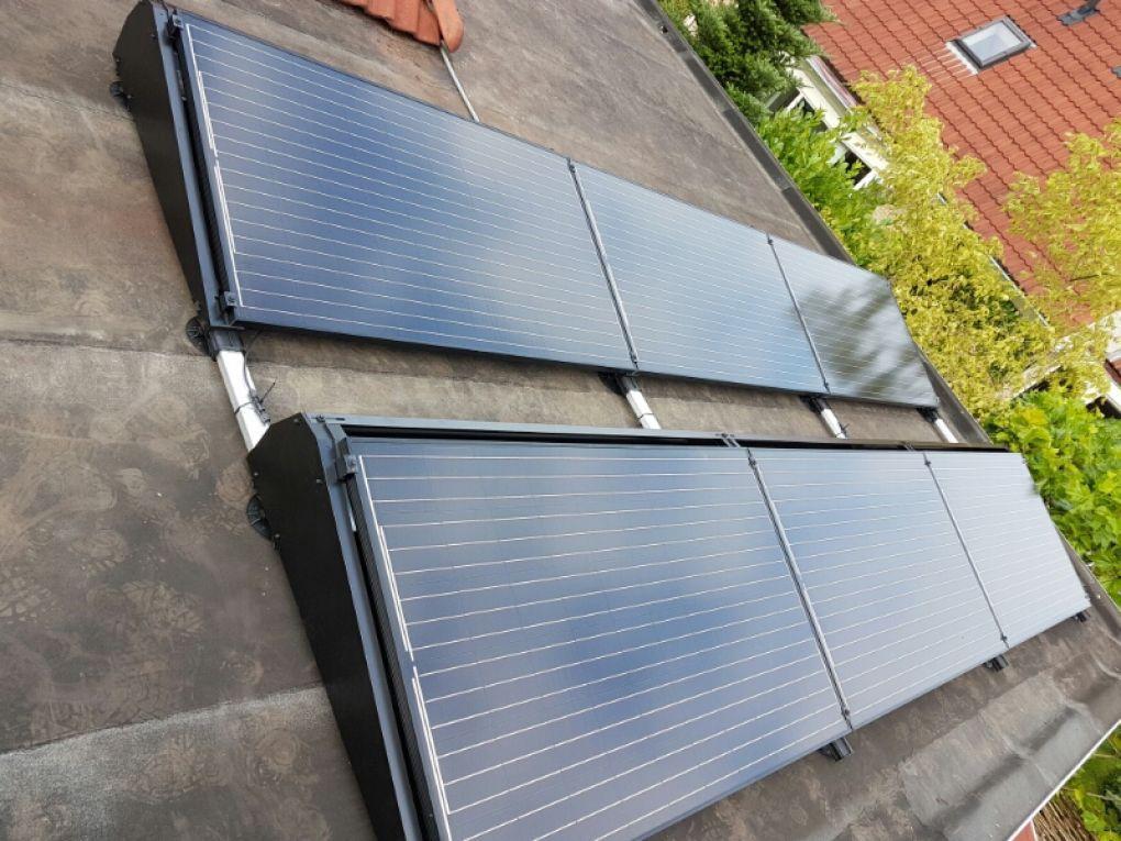 Zwarte zonnepanelen geplaatst op schuin en plat dak te assen