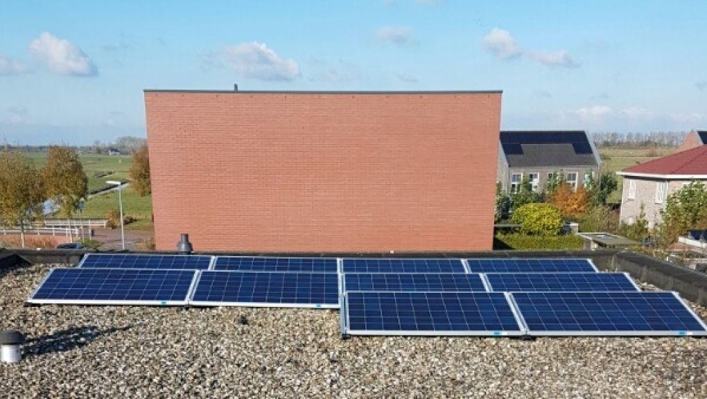 Blauwe zonnepanelen geplaatst op een plat dak te groningen in